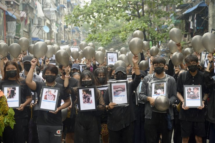 Anti-coup protesters holding pictures of those who died during a protest against the military offer prayers for them in Yangon, Myanmar, Monday. AP-Yonhap