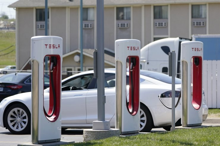 In this April 5 file photo, a Tesla electric vehicle charges at a station in Topeka, Kan. With strong sales of its electric cars and SUVs, Tesla on Monday posted its seventh-straight profitable quarter. AP-Yonhap