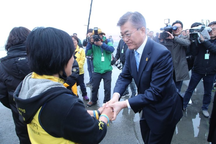 In this photo from April 6, 2017, then-presidential candidate Moon Jae-in from Democratic Party shakes hands of a person whose family member had gone missing from the Sewol ferry disaster in 2014 at a harbor in Mokpo, South Jeolla Province. Korea Times file