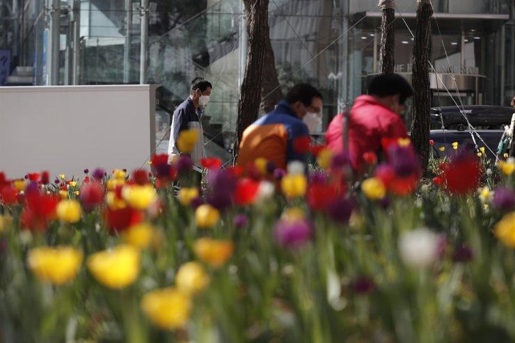 Men wear face masks as a precaution against COVID-19 past in a park in Seoul, April 8. AP
