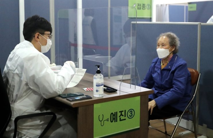 An elderly woman goes through a preliminary medical examination with a doctor ahead of her COVID-19 vaccination at a vaccination center in Busan, April 1. Yonhap