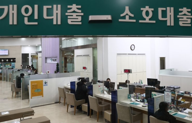 In this photo from Jan. 10, 2021, visitors to a bank in Seoul talk to tellers handling loans. Yonhap