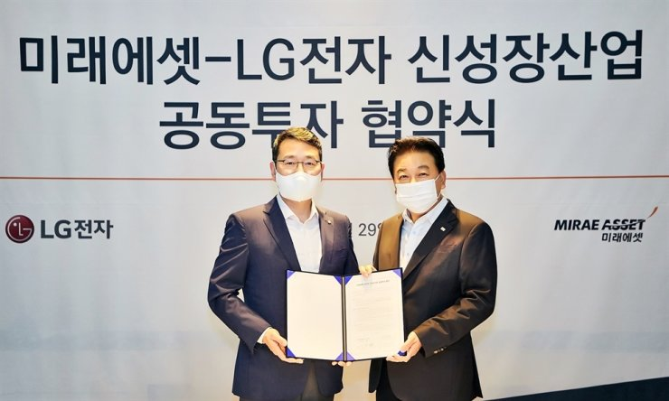 LG Electronics Chief Strategy Officer Cho Ju-wan, left, Lee Man-hee, head of Mirae Asset Capital, pose for a photo after agreeing to invest in new businesses at the Four Seasons Hotel Seoul, Thursday. Courtesy of LG Electronics