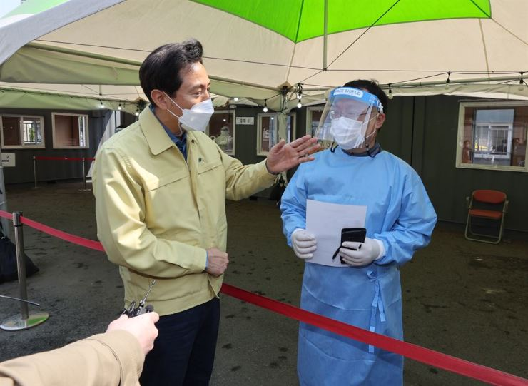 Newly elected Seoul Mayor Oh Se-hoon, left, speaks with a quarantine official at a makeshift coronavirus testing clinic at Seoul Station, Saturday. Yonhap