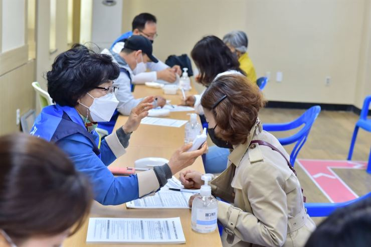 Medical staffers examine citizens before COVID-19 inoculation at a vaccination center on Jeju Island, Wednesday. Yonhap