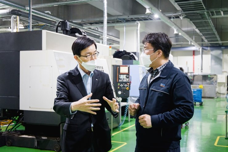 Export-Import Bank of Korea (Eximbank) CEO Bang Moon-kyu, left, talks with an official from DSTECHNO, a local semiconductor materials firm, during his visit to the company located in Icheon, Gyeonggi Province, Wednesday. Bang promised that the state-run bank would continue to offer financial support for domestic semiconductor businesses. / Courtesy of Korea Eximbank