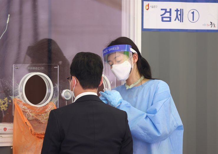 A medical worker takes test samples for COVID-19 at a makeshift testing center near Seoul Station in central Seoul, April 22. Yonhap