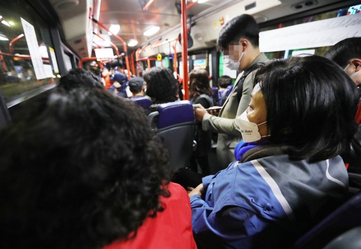 The ruling Democratic Party's Seoul mayoral candidate Park Young-sun, right, heads to Noryangjin Fish Market in Seoul's Dongjak District in the early morning of April 6 in a public transit bus. Courtesy of Park Young-sun's election camp