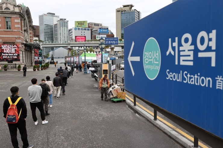 People wait in line to receive COVID-19 tests, Sunday, at a makeshift testing center in front of Seoul Station. Yonhap