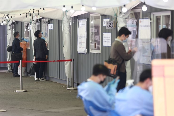 Medical workers take test samples for COVID-19 at a makeshift testing center near Seoul Station in central Seoul, April 26. Yonhap