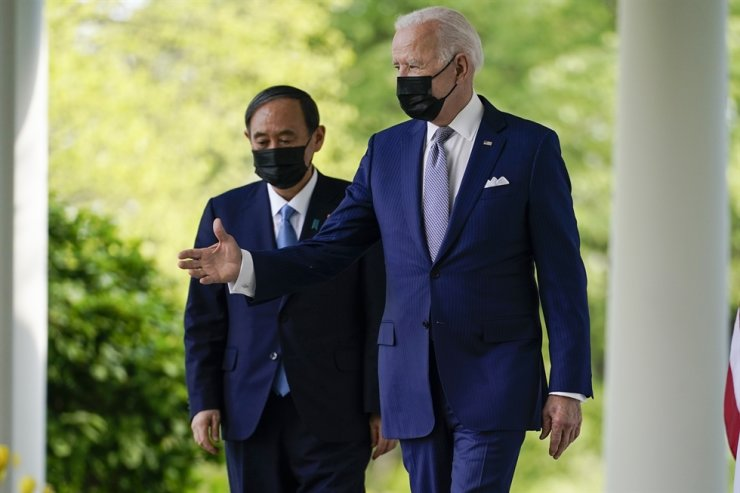 President Joe Biden, accompanied by Japanese Prime Minister Yoshihide Suga, walks from the Oval Office to speak at a news conference in the Rose Garden of the White House, Friday. AP-Yonhap