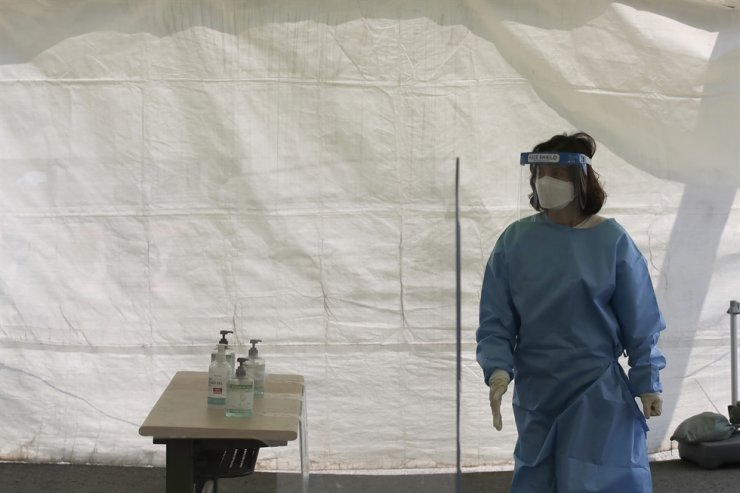 A health official wearing protective suits waits visitors at a temporary screening clinic for coronavirus in Seoul, April 10. AP
