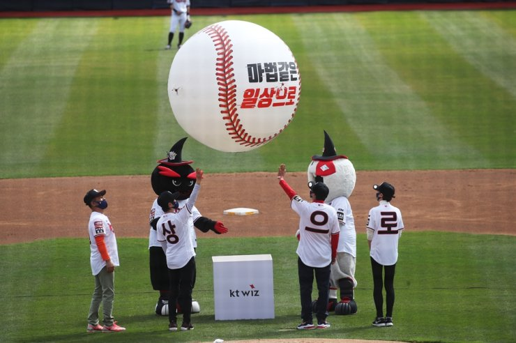 In a rare style of first pitch at KT Wiz Park in Suwon, Gyeonggi Province, ahead of a Korean Baseball League match between KT Wiz and Hanwha Eagles on April 4, merchants of the city's Jowon traditional market float a giant air balloon in shape of a baseball with a text that reads 'Into the magical daily lives' in hopes of cheering the country's business owners who were hit by COVID-19's economic impact. Yonhap