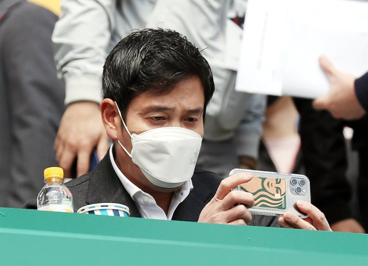 Shinsegae Vice Chairman Chung Yong-jin takes a photo in his seat during the baseball match between SSG Landers and Lotte Giants at SSG Landers Field in Incheon, April 4. Yonhap