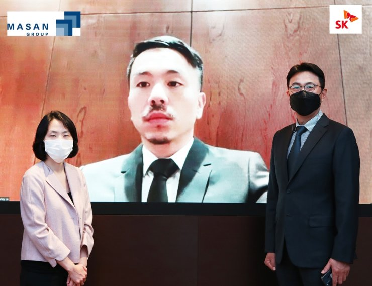 SK South East Asia Investment Managing Director Park Won-chul, right, and Vice President Kwon Hye-jo, left, pose with Masan Group CEO Danny Le on screen at SK's building in central Seoul, Tuesday, after signing a deal about SK's investment in Masan's retail unit, VinCommerce. Courtesy of SK