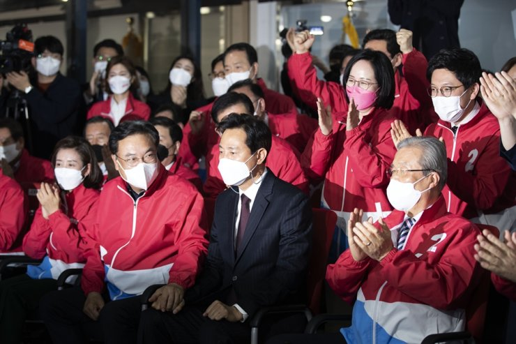 Members of the main opposition People Power Party cheer at party headquarters on Yeouido, Seoul, Wednesday, as the exit poll for the Seoul mayoral by-election showed a likely victory for the party's candidate Oh Se-hoon, front row second from right. Korea Times photo by Choi Won-suk