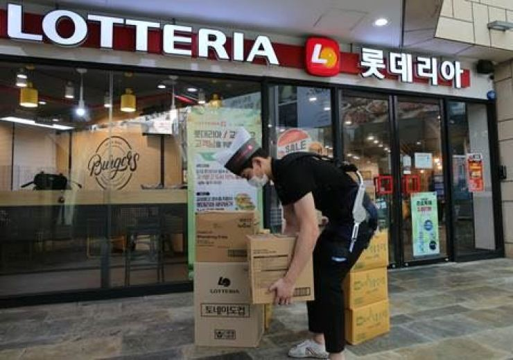 A clerk moves boxes in front of a Lotteria chain store in Seoul's Jamsil last October.  Korea times file