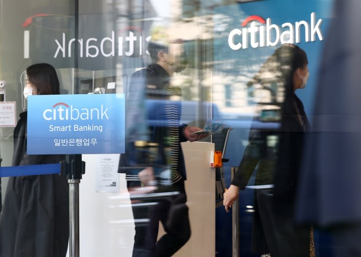Citibank Korea employees walk around in its head office in Seoul, Monday. Yonhap