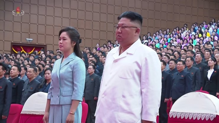 North Korean leader Kim Jong-un, right, stands with his wife Ri Sol-ju during a ceremony to mark the birthday of his grandfather, North Korea founder Kim Il-sung, on April 15, in this footage from an April 17 TV report by Pyongyang's Korean Central Television. Yonhap