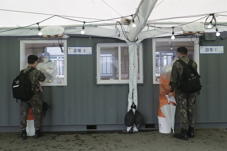 Medical workers in booths take nasal samples from Army soldiers at a coronavirus testing site in Seoul, April 12. AP