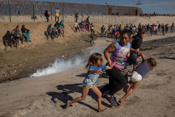 Maria Meza, a 40-year-old migrant woman from Honduras, part of a caravan of thousands from Central America trying to reach the United States, runs away from tear gas with her five-year-old twin daughters Saira Mejia Meza, left, and Cheili Mejia Meza, right in front of the border wall between the U.S and Mexico, in Tijuana, Mexico, Nov. 25, 2018. This is a winning photography at the Pulitzer Prize's breaking news photography award for 2019. Reuters-Yonhap