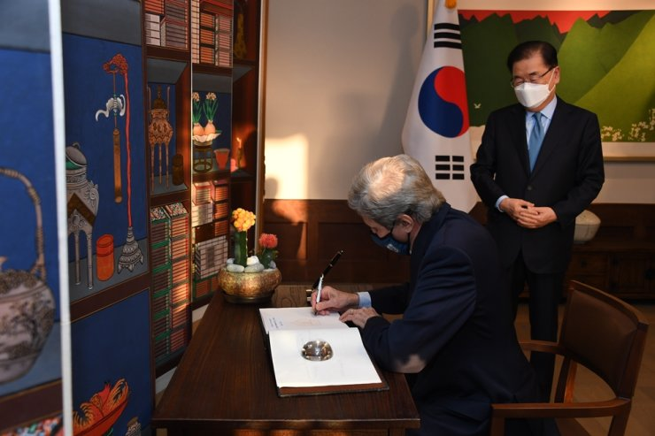 A handout photo made available by the US Embassy in Seoul shows US Special Presidential Envoy for Climate John Kerry, left, signing a guest book and South Korean Foreign Minister Chung Eui-yong watches at the Foreign Minister's residence in Seoul, April 17. EPA-Yonhap