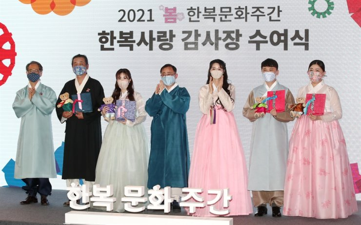 Participants pose during an award ceremony to give a certificate of appreciation to those who contributed to promoting Korea's traditional hanbok attire, at the Dongdaemun Design Plaza in Seoul, Monday. From left are Korea Craft & Design Foundation President Kim Tae-hoon, Netflix series 'Kingdom' costume designer Kwon Yoo-jin, K-pop singer and actress Jun Hyo-seong, Vice Minister of Culture Oh Young-woo, hanbok ambassador Kwon Na-ra, Lakai Korea CEO Shin Jung-hun and Riot Games PR leader Gu Gi-hyang. Yonhap