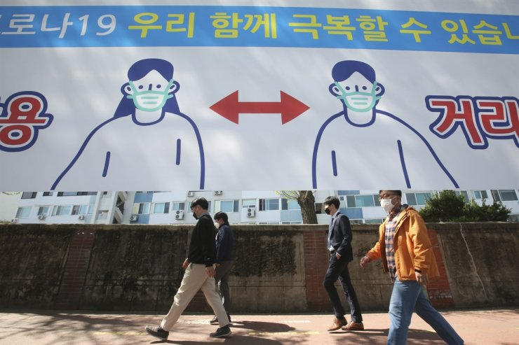 People wearing face masks pass by a banner displaying precautions against the coronavirus on a street in Seoul, April 5. AP