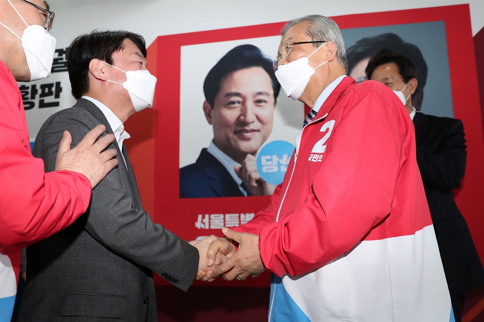 Oh Se-hoon, center, the main opposition People Power Party's candidate for Seoul mayor, closes his eyes while receiving applause and affirming touches from party members at the party headquarters in Seoul, Wednesday, after exit polls showed a likely victory for him. Yonhap