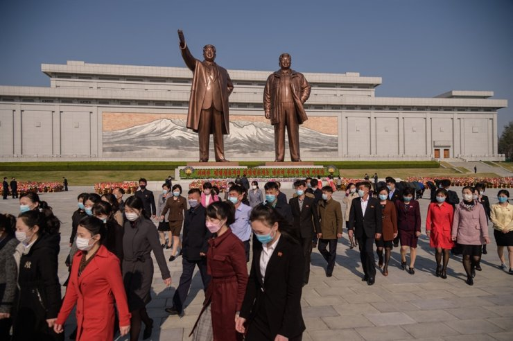 People leave after paying their respects before a statue of Kim Il-sung, left, as North Korea marks the 109th birth anniversary of the late leader, known as the 'Day of the Sun,' at Mansu Hill in Pyongyang, April 15. AFP