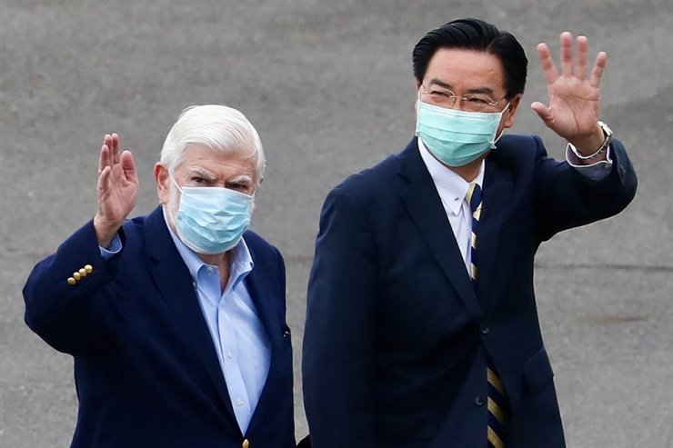 This handout picture taken and released by Taiwan's Ministry of Foreign Affaires (MOFA) on Wednesday shows former U.S. senator Christopher Dodd, left, and Taiwan's foreign minister Joseph Wu waving after the arrival of an unofficial U.S. delegation at Songshan Airport in Taipei. AFP-Yonhap