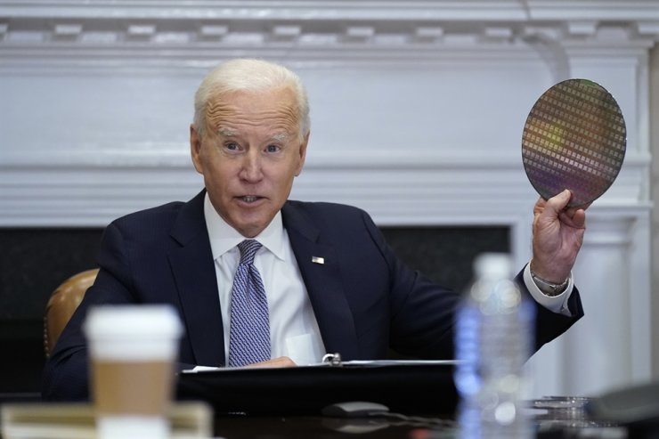 U.S. President Joe Biden holds up a silicon wafer as he participates virtually in the CEO Summit on Semiconductor and Supply Chain Resilience in the Roosevelt Room of the White House, April 12, in Washington. AP