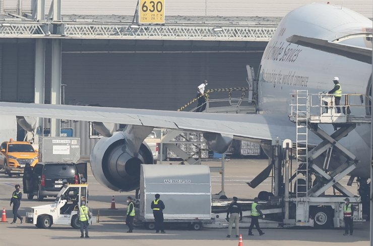 Work to unload 250,000 doses of Pfizer's COVID-19 vaccine from a UPS cargo plane is under way at Incheon International Airport, Wednesday. Yonhap