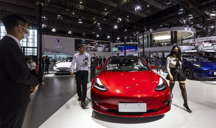 People walk by the Tesla Model 3 car at the Tesla trade fair stand during a media day of the Auto Shanghai 2021 motor show in Shanghai, China, April 19. EPA-Yonhap