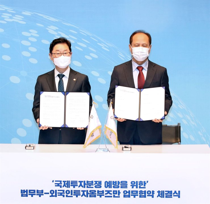 KOTRA's Foreign Investment Ombudsman Kim Sung-jin, right, poses with Justice Minister Park Beom-kye after signing a memorandum of understanding to cooperate on preventing investor-state disputes at the former's headquarters in southern Seoul, Friday. Courtesy of KOTRA