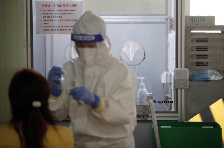 A medical worker takes test samples for COVID-19 at a testing center in Gwangju, April 30. Yonhap
