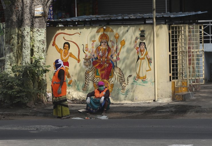 Municipal workers wearing face masks as a precaution against coronavirus take rest in front of a Hindu temple in Hyderabad, India, Monday. AP-Yonhap