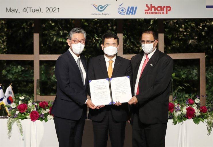 Incheon International Airport Corp. President and CEO Kim Kyung-wook, center, holds a memorandum of agreement with Yossi Melamed, right, general manager of the aviation group of Israel Aerospace Industries, and Paik Soon-suk, CEO and president of Sharp Technics K, during a signing ceremony at Paradise City in Incheon, Tuesday. Courtesy of Incheon International Airport Corp.