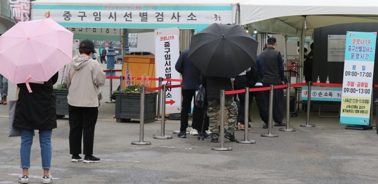 People stand in line to get a coronavirus test at a makeshift testing center in front of Seoul station, Thursday. Yonhap