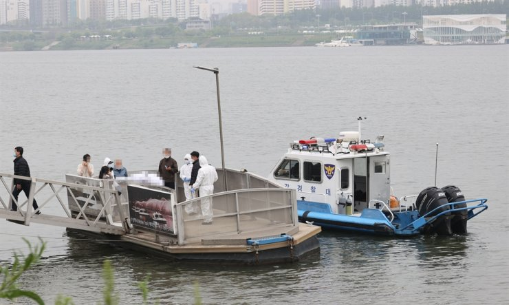 Police officers recover the body of a college student, who was reported missing, near the Banpo Han River Park in southern Seoul, April 30. Yonhap