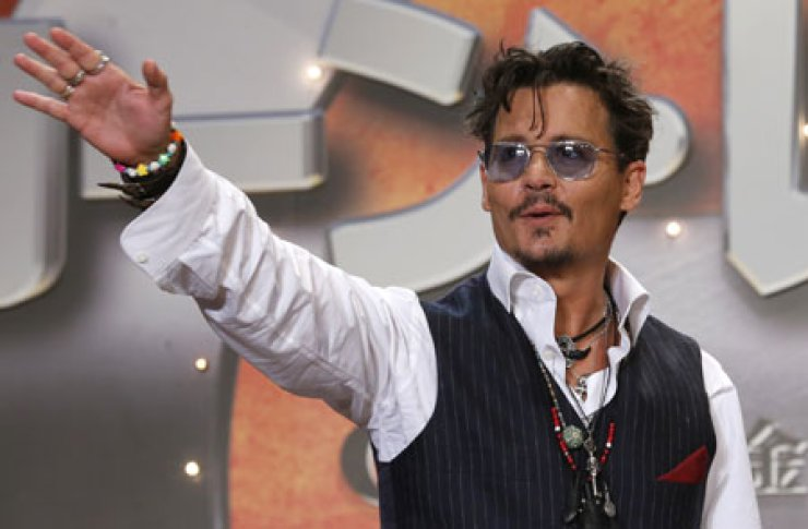 Actor Johnny Depp waves to fans during the Japan premiere of his film 'The Lone Ranger' in Tokyo, Wednesday./ AP-Yonhap