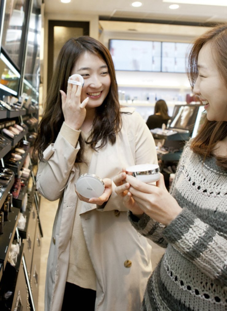 Cusotmers try on AMOREPACIFIC's IOPE 'Air Cushion' at a Aritaum road shop in Seoul.