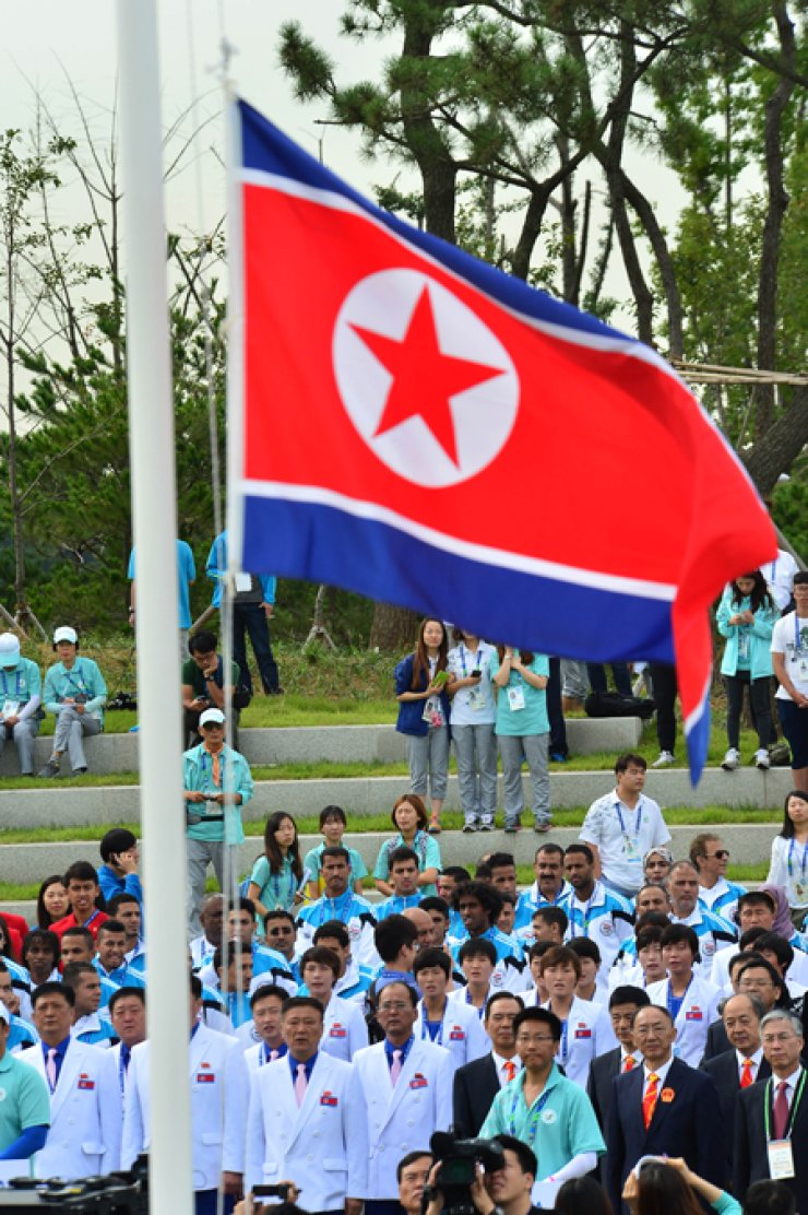 Athletes of the North Korean delegation for the Incheon Asian Games watch the country's national flag being hoisted during a welcoming ceremony at the Flag Plaza in the Athletes' Village in Guwol-dong, Incheon, on Thursday morning, one day before the Asiad's opening. / Korea Times photo by Shim Hyun-chul
