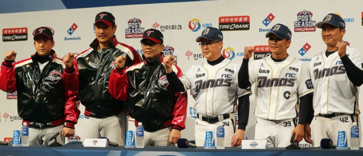 Kim Kyung-moon, third from right, manager of the NC Dinos, and Yang Sang-moon, third from left, manager of the LG Twins, pose with their players during a media conference for the Korea Baseball Organization's (KBO) second playoff round at the Masan Baseball Stadium in Changwon, South Gyeongsang Province, Thursday. The two teams will begin their best-of-five series today.  / Yonhap