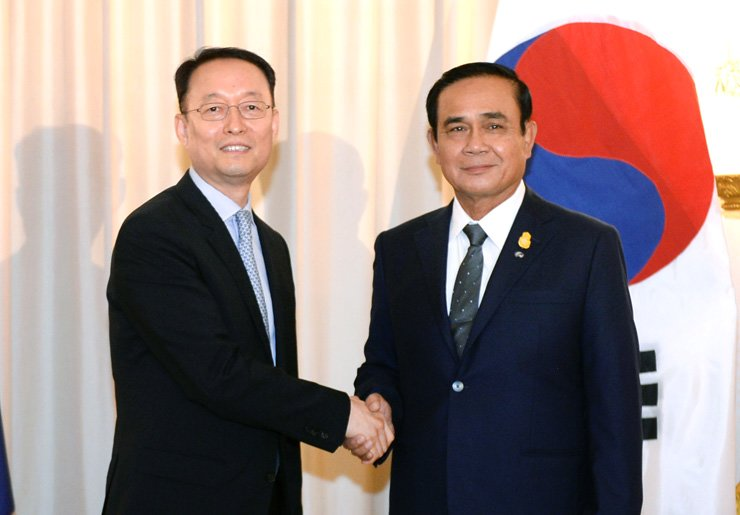 Paik Un-gyu, South Korean minister of trade, industry and energy, left, shakes hands with Thailand's Prime Minister Prayuth Chan-ocha after their meeting in Bangkok, Wednesday. / Yonhap