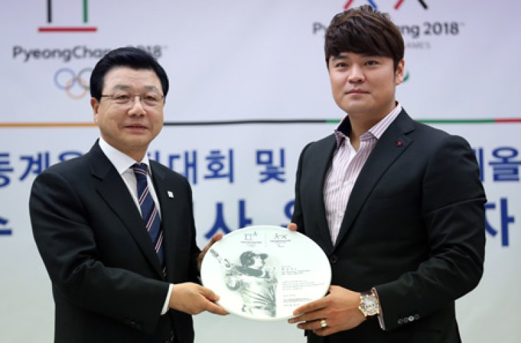 Texas Rangers' Choo Shin-soo, right, and Kim Jin-sun, president of the 2018 PyeongChang Olympic organizing committee, pose with a commemorative plate after Choo was named a goodwill ambassador for the event at the Korea Press Center in Seoul, Monday. / Yonhap