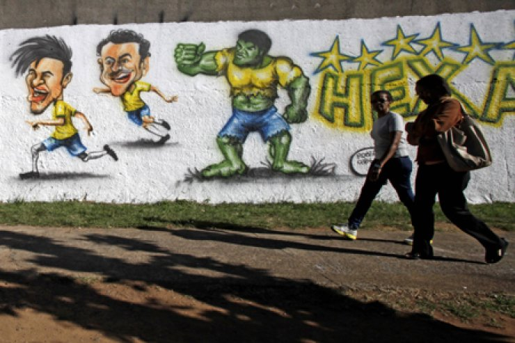Passersby walk past a wall decorated with a mural depicting soccer player Neymar of Brazil during the 2014 soccer World Cup in Indaiatuba, near Sao Paulo, Wednesday. / AP-Yonhap