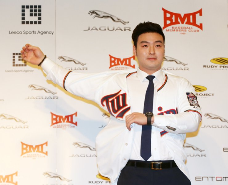 Park Byung-ho puts on the Minnesota Twins uniform at a press conference in the Grand Hilton Seoul Hotel, Thursday. / Yonhap
