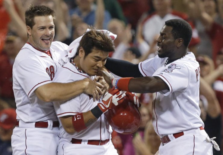 Cincinnati Reds' Choo Shin-soo, center, is congratulated by left fielder Chris Heisey, left, and second baseman Brandon Phillips after Choo hit a walk-off single in the 11th inning of a game against the San Francisco Giants in Cincinnati, Wednesday. / AP-Yonhap
