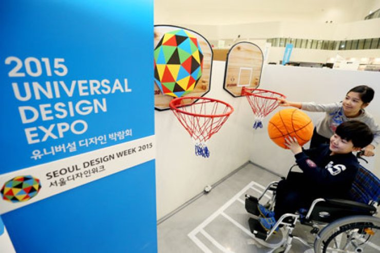 A boy tries to shoot a basket designed to be wheelchair-friendly at the '2015 Universal Design Expo'  which opened at the Dongdagemun Design Plaza (DDP), as part of the '2015 Seoul Design Week,' Wednesday. / Yonhap